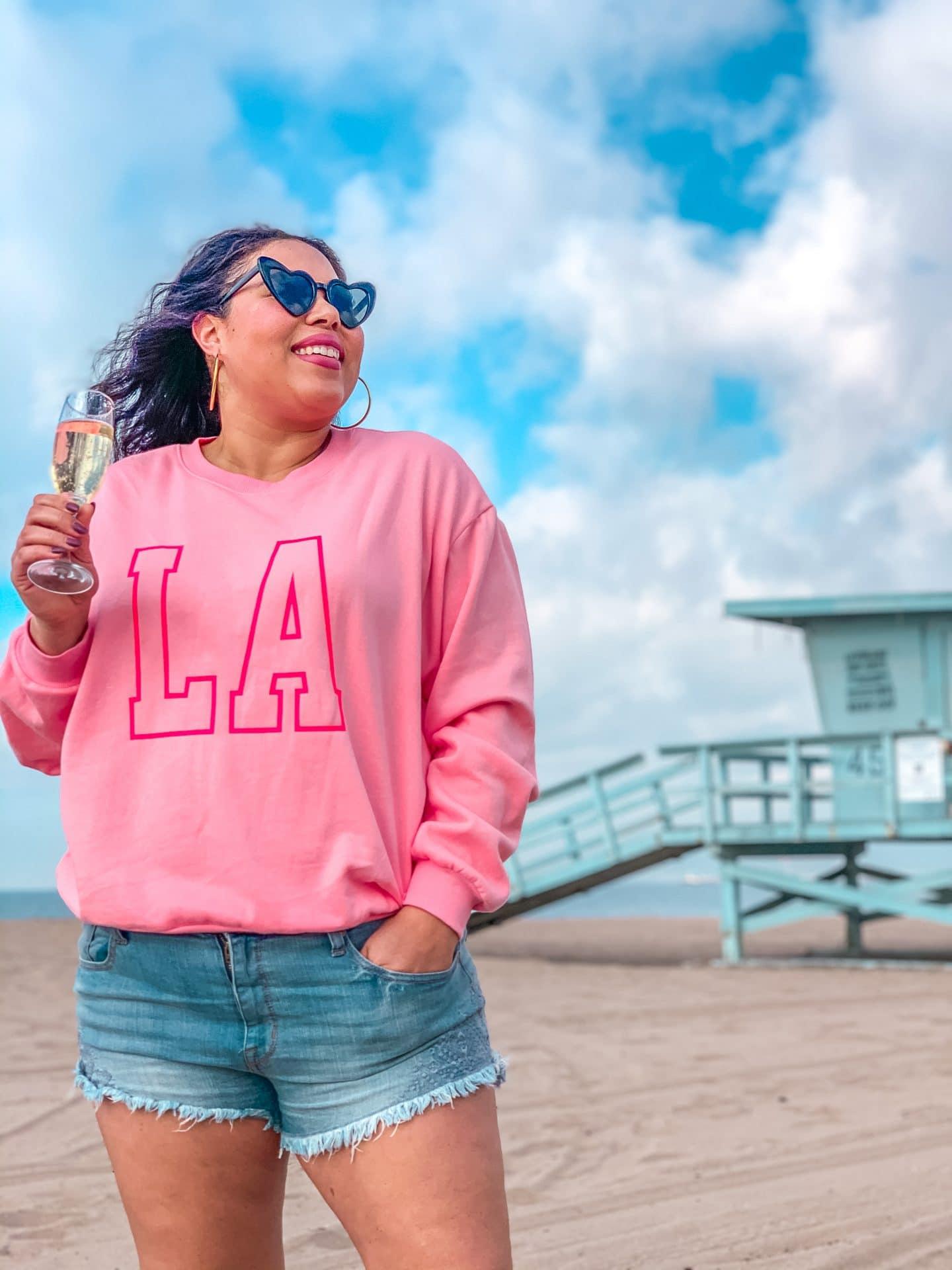pink la sweatshirt and jean shorts on los angeles, playa del rey beach